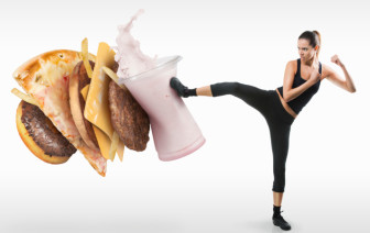 Fit young woman fighting off fast food